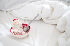 Cumbuca natalina de papai noel na cama com edredom e lençol branco.