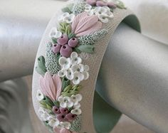 Wide floral bangle bracelet. Yellow tulips and green leaves on a pale blue background. Large bright flowers create a summer mood. Massive bracelet fashioned of polymer clay. All details are hand-sculptured. Pleasant to the touch texture. Inner diameter 2,5 inches (65 mm) size M, width 1,6 inches (40 mm) You can order in other size Weight 65 g Water-resistant Suitable earrings: https://www.etsy.com/ru/listing/240953561/ More similar bracelets: https:/...