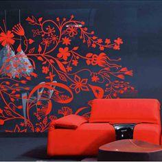 Sofá rojo, mesa de madera rojiza y decoración florarl en las paredes roja. Pero todo sobre fondo negro