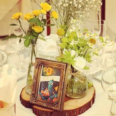 ガラスの瓶に野花を詰め込んだようなフラワーアレンジ* 切り株の上にセットしたナチュラルさが会場にぴったりです。 花はかすみ草、ゴールドスティック、ミニバラ、マトリカリア* ご新郎さまが選ばれたテーブルマークの写真もお洒落です♡