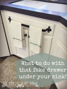 What to do with that fake drawer under your kitchen sink. Kitchen cabinet towel bar and other kitchen hacks at the Domestic Heart blog.
