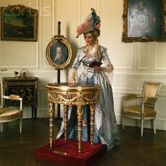 A wax figure of Marie Antoinette admires the Table of Teschen in the Chateau de Breteuil.