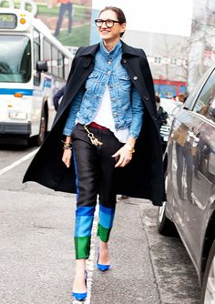 Jenna Lyons' wearing a long black coat draped over the shoulders with a denim jacket underneath