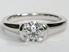 Modern style solitaire engagement ring with the diamond in a half bezel setting. This is