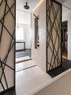 This neutral bathroom area has an open shower that allows for easy transition between the main bathroom and vanity areas. Black fixtures, including an overhead rain shower head, are featured in the shower, complementing the contemporary metal wall-frame art installation that lines either side of the shower entrance.