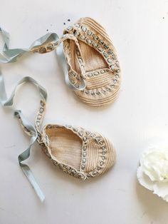 This pair of baby booties has been delicately crocheted with a fine, off-white thread to fit to the babys feet. A pale blue ribbon is