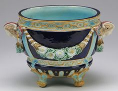 Joseph Holdcraft majolica jardinière in the Neoclassical taste, circa 1870,  having a geometric mustard band at the rim with floral swags on a cobalt ground, with high relief female mask handles, the interior glazed in turquoise, and the whole rising on outswept feet, marked with an impressed JH in a circle.