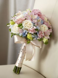 Blooming with sweet sentiments and endearing charm to get you to look your bridal best on your wedding day. Stunning cream roses, pink mini carnations, pink alstroemeria, pink double lisianthus, blue hydrangea and bupleurum are brought together to create a picture-perfect bouquet. Tied together with a soft peach satin ribbon accented with pixie pearl pins, this incredible styling culminates in a bow at the base of the bouquet. Approx. 16