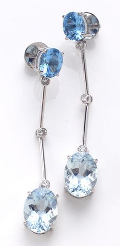 A pair of aquamarine, blue topaz, diamond and eighteen karat white gold earrings each pendant earring designed with an oval-shaped blue topaz, suspending collet-set round brilliant-cut diamonds, terminating with an oval-shaped aquamarine; estimated total aquamarine weight for the pair: 14.00 carats.
