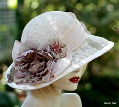 Womens Vintage Style Fancy Formal Wide Brim Straw Hat for Summer. A vintage style design for a vintage inspired hat for weddings, formal high tea party or gala event. The hat's crown has a buckram frame covered in chiffon over layered with a floral print lace. The hat is in a soft ivory decorated with a soft pink pleated taffeta band accented with a over sized multi colored flower surrounded by smaller accent flowers in mauve, ivory and taupe. The brim has been hand sculpted to measure…