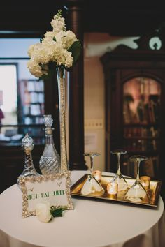 Our bar area was decorated with simple, gold touches. An eiffle-tower vase was filled with pearls and topped with white hydrangeas to finish off this high-top table display.   See the rest of our Gatsby themed wedding, here! http://issuu.com/inbliss/docs/in_bliss-_pre-fall_2013?e=8049904%2F4363659