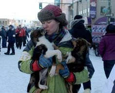 Sarah Keefer holds two puppies during the ceremonial start of the 2017 Iditarod. Ryan Redington's Idita-Rider Annika, a Make-A-Wish 10-year-old from Wisconsin, will get to name the pups, which are from Raymie Redington's kennel. (Bob Hallinen / Alaska Dispatch News)