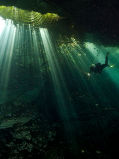 Divers exploring an underwater cave in a cenote. PAUL NICKLEN/National Geographic Stock