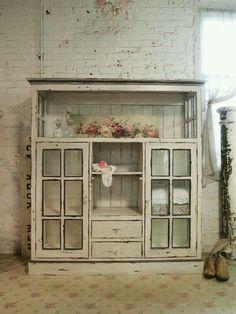 Armario blanco con puertas acristaladas.