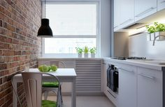 weiße Küchenzeile, roter Backstein und grüne Akzente