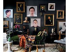Antique and contemporary collection of portraits adorns a black wall