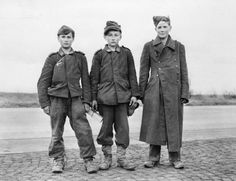 Three 14 year-old German prisoners of war captured by 6th Armoured Division, Third US Army, near Giessen, 30 miles north of Frankfurt-am-Mai...