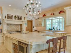 The main kitchen was built for entertaining. In the center is a large, marble-topped island with a built-in prep sink on one side and seating on the other. The kitchen has two dishwashers, a double oven, and a wine cooler.