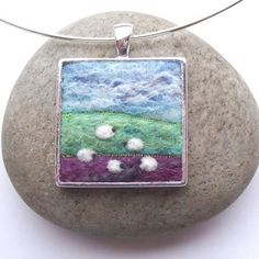 Felt Landscape Necklace with Sheep by Aileen Clarke: Pure merino wool & silk fibres were used for the sky & clouds & mixed fleece fibres from the Orkney Island of North Ronalsay for the foreground & tree. A little bit of machine stitch adds detail, while the sheep & tree are needle felted on by hand.