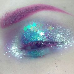 pink eyebrow with glitter and sparkles over irredescent blue and purple eyeshadows with a matte blue-rose colour surround and cerise mascara