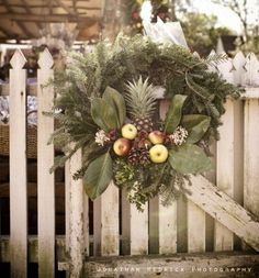 Great wreath with cluster of fruit. Baby pineapple and magnolia leaves. Colonial fence.