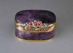 Rectangular hinged amethystine quartz snuff box, mounted with gold rim and base tooled with guilloché decoration, large floral thumbpiece of gold set diamonds and rubies. Interior solid amethystine quartz with beautifully moulded base. Germany, c.1770.