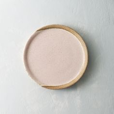 Satin pale pink wheel thrown speckled plate Measures 9.25inches in diameter. Food and dishwasher safe. Hand washing recommended. Glaze patterns vary.