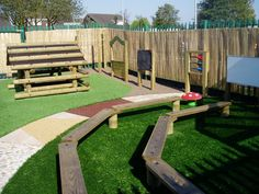 Nursery Area - In this design the original plain tarmac playground has been transformed into a variety of new 'natural' play environments. The textured surface provides tactile and auditory experiences and also acts as a natural perimeter to the different parts of the playground. To maximise the sensory experiences the area includes artificial grass, mark making boards, play panels, a music frame, a mirror and an imagination frame for den making.