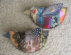 Fabrics used are scraps of silk on the top one, and faux leather animal prints on the lower one. Seams are covered by sewing on bits of ribbon, trim and fibers. I used a real feather for the wing on the lower one.
