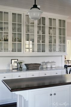 Spectacular cottage kitchen design with glass-front cabinets and white lower cabinets paired with marble countertops and beadboard backsplash as well as schoolhouse pendants over butcher block kitchen island. Cottage kitchen features white plank ceiling, woven basket and clear glass canisters.