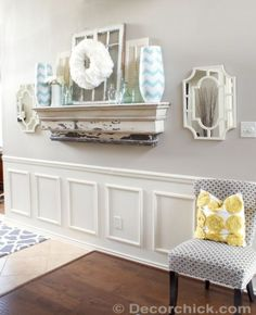 Emily of Decorchick! used a chair rail, wooden frames, caulking, and several coats of white paint to create this wainscoting look-alike.