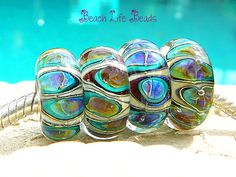 Lampwork Torus Bead. lush turquoise, aqua, purple and lime on a base of ivory heavily encased in crystal clear for huge magnification of colors. Bright fun color combination!