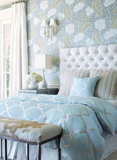 Relaxing bedroom in blue and grey with a beautiful white upholstered bed