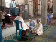 A group of old men relaxing inside the Shait Gumbad Mosque (1459) in Bagerhat, Bangladesh.