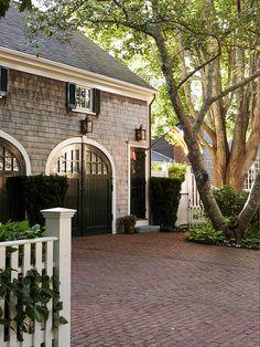 Brick driveway, carriage house doors, shingle siding, lanterns
