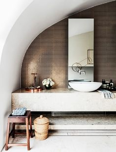 The curved ceiling of this Sydney bathroom makes the room, but the copper penny round tile backsplash is the showstopper. The bathroom is accessorized with more copper accents, as well as raw organic materials to give it a laid-back feel.