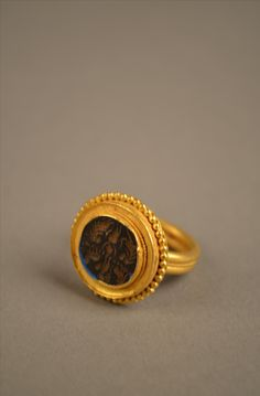A Greek hellenistic Heavy And Sollit Gold Ring circa 200 B.C. a stunning greek sollit heavy gold ring with black agaat stone in the center.
