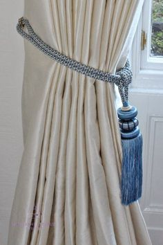 These interlined silk curtains were handmade for a home in Edinburgh. The blue tassel tiebacks add a little splash of colour to the window treatment as well as making it fit seamlessly into the colour scheme of the room.  #HandmadeCurtains #WindowTreatments #SoftFurnishings #SilkCurtains #InterlinedCurtains #BlueTasselTiebacks #Tiebacks