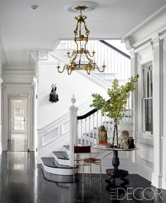 The entry's bronze chandelier is original to the house, as are the wood floors, which are stained ebony; the chair was found in a Brussels antiques market, and the walls are painted in Benjamin Moore's Decorators White.