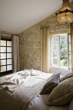 French farmhouse style bedroom with stone wall and crystal chandelier on Hello Lovely Studio