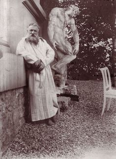 French sculptor Auguste Rodin (1840 - 1917) in the garden of his villa at Meudon, near Paris. Behind him is the original plaster statue of The Creation of Man. Edward Gooch, circa 1900.