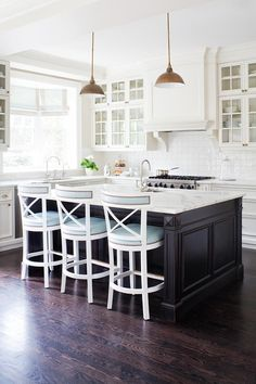 nailhead trim stools, dark floors and island, white glass cabinets ♥