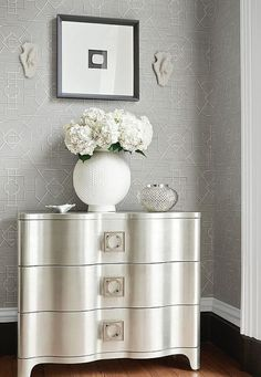 Gorgeous silver and white features walls lined with gray Thibaut Eastgate wallpaper holding a black framed black and white print hung above a Modern Classic antique silver leaf nightstand fitted with decorative metal pulls. Grey Trellis Wallpaper, Glam Wallpaper, Wallpaper Grasscloth, Oriental Wallpaper, Beautiful Wallpaper, Textured Wallpaper, Wallpaper Ideas, Foyer Decorating, Decorating Bedrooms