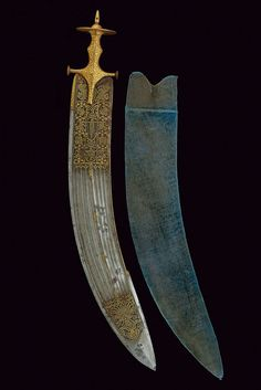 Indian thega Sword, 19th century  Measurements: overall length 87.5 cm The sword has a wide, curved, single-and false-edged blade. The first part is engraved with gilt figures, tigers and birds among floral elements; it has nine grooves at the center, three thin grooves at the back, the tip featuring a cartouche engraved with a deity, damask surface, the opposite side decorated en suite. The big tulwar grip has a wide disk-pommel featuring gilt inlays and floral motifs, green velvet…