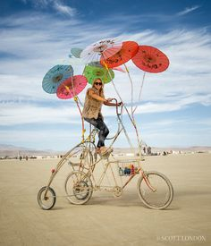 A woman rides a modified bike with multicolored parasols at Burning Man 2016. (Photo by Scott London)