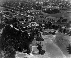 (1924)* - Aerial view of the second Raymond Hotel looking across the grounds at the western facade, the main entrance to the hotel. Extensive urban development can be seen in the background.	  Water and Power Associates