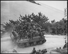 Tank-borne infantry moving up to take the town of Ghuta before the Japanese can occupy it. The men are members of the 29th Marines. Okinawa April 1 1945.