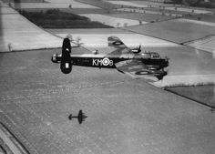 Lancaster B Mark I, of No.97 Squadron RAF, piloted by Squadron Leader J D Nettleton of No. 44 Squadron RAF, flying at low-level over the Lincolnshire countryside during a Squadron practice for the low-level attack on the M.A.N. diesel engineering works at Augsburg, which took place on 17 April 1942.