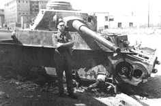 A British soldier strikes a formal pose with a wrecked Pz.Kpfw.IV Ausf.H. The tank was knocked out while at a road junction by a hit to the final drive. Another A.P. projectile has embedded itself in the driver's front plate, just next to the radio operator's position and can be seen sticking out! The tank was subsequently stripped of all useful parts.