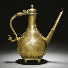 Cast bronze ewer and cover, Mughal, India, 18th century:  pear-shaped body on pedestal base standing on four small feet, with a straight spout and serpentine handle with dragon and lion-head terminals, including a hinged domed cover, decorated with plain chiselled lotus petals to base and neck .